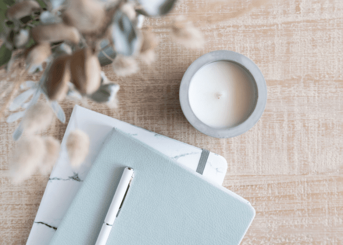 desk dried flowers blue notebook white pen white candle