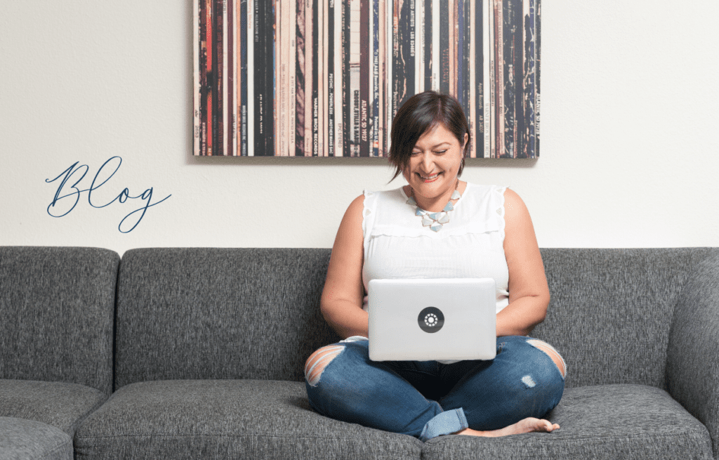 woman in white shirt on gray couch with laptop